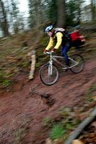 A female biker rides in the mud. - Paul Box - 02-02-2004