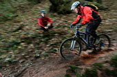 A mountain biker rides in the mud, watched by an instructor - Paul Box - 02-02-2004