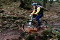 A female mountain biker rides in the mud. - Paul Box - 02-02-2004