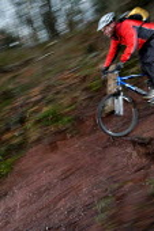 A male mountain biker rides in the mud. - Paul Box - 02-02-2004