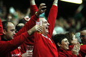 Welsh rugby fans celebrate winning against Scotland in the 5 nations rugby union tournament at the Millennium Stadium Cardiff, Wales - Paul Box - 2000s,2004,against,celebrate,celebrating,celebration,celebrations,cheer,cheering,cheers,color,colorful,colorfull,colors,colour,colourful,colours,crowd,crowds,cyrmu,exaltant,fan,fans,female,five,game,g