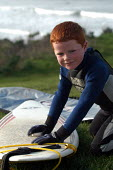 Ginger haired boy waxs surfboard before going surfing at Woolacombe in Devon - Paul Box - 12-02-2004