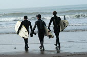Three friends walk down the beach with surfboards, Woolacombe in Devon - Paul Box - 12-02-2004