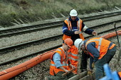 Railway engineers working on railway lines near Bristol - Paul Box - 2000s,2004,apparel,cable,cables,capitalism,capitalist,cities,city,clothing,contractor,contractors,EBF Economy,EMPLOYEE,employees,engineer,engineering,engineers,hard hats,Industries,industry,infrastruc
