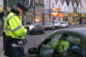 Parking attendant writes a parking ticket in a clearway zone for bus route, Bristol - Paul Box - 03-03-2004