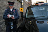 A newly trained parking attendant writes a parking ticket for a taxi , Bristol - Paul Box - 03-03-2004