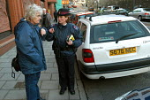 A woman parking attendant gives directions to an elderly lady, Bristol - Paul Box - 03-03-2004
