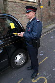 A parking attendant supervisor issues a parking ticket for a taxi , Bristol - Paul Box - 03-03-2004