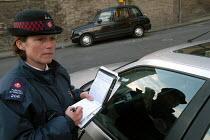 A woman parking attendant, Bristol, issues a ticket. - Paul Box - 2000s,2004,attendant,attendant attendants,ATTENDANTS,car cars,cities,city,civil enforcement officer,contro,council services,council services,council worker,employee,employees,Employment,europeregi,FEM