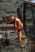 Rail workers working on railway lines. - Paul Box - 2000s,2004,apparel,capitalism,capitalist,clothing,EBF Economy,EMPLOYEE,employees,ENGINEER,engineers,great,hard hats,hat,Industries,industry,LAB LBR work,laying,line,lines,maintaining,Maintenance,maker