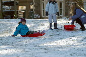 A Child sledging, St Andrews park , Bristol - Paul Box - 2000s,2004,adult,adults,at,child,CHILDHOOD,children,Council Services,Council Services,families,FAMILY,FEMALE,juvenile,juveniles,kid,kids,landscape,LANDSCAPES,local authority,MATURE,mother,MOTHERHOOD,M