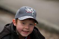 A boy sits on pavement wearing baseball cap - Paul Box - 20-03-2004