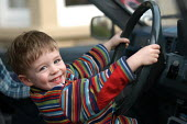 A young boy sits in the driving seat of dads car - Paul Box - 2000s,2004,a,appealing,at,AUTO,AUTOMOBILE,AUTOMOBILES,AUTOMOTIVE,boy,boys,car,cars,charming,child,CHILDHOOD,children,cute,drive,driver,drivers,driving,EMOTION,EMOTIONAL,EMOTIONS,enjoying,enjoyment,fam