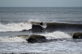 A surfer , surfing on the north coast of Devon in the winter. - Paul Box - 01-03-2004