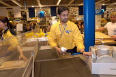 Ikea home furnishing store, a employee works at the check out - Paul Box - 2000s,2004,asian,assistant,assistants,BAME,BAMEs,black,BME,bmes,bought,buy,buyer,buyers,buying,checkout,commodities,commodity,consumer,consumers,customer,customers,diversity,EARNINGS,EBF Economy,EQUAL