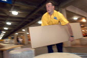 Ikea home furnishing store, loading area. An employee helps load flat pack furniture into a customers car - Paul Box - 2000s,2004,assistant,assistants,board,bought,box,boxes,buy,buyer,buyers,buying,card,commodities,commodity,consumer,consumers,customer,customers,EARNINGS,EBF Economy,EQUALITY,flat,furnishing,furniture,