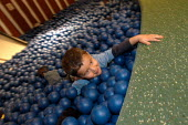 Ikea home furnishing store, a child plays in the instore creche - Paul Box - 2000s,2004,ball,balls,boy,BOYS,care,carer,carers,child,CHILD CARE,childcare,CHILD-CARE,CHILDHOOD,CHILDMINDING,children,CRECH,creche,CRECHES,Customer,Customers,EARLY,early years,facility,home,ikea,juve