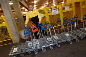 Ikea home furnishing store, loading area. An employee moves trollies. - Paul Box - 2000s,2004,assistant,assistants,bought,buy,buyer,buyers,buying,commodities,commodity,consumer,consumers,customer,customers,design,EARNINGS,EBF Economy,EQUALITY,furnishing,goods,home,ikea,Income,INCOME