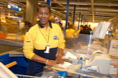 Ikea home furnishing store, a employee works at the check out - Paul Box - 2000s,2004,assistant,assistants,BAME,BAMEs,black,BME,bmes,bought,buy,buyer,buyers,buying,checkout,commodities,commodity,consumer,consumers,customer,customers,diversity,EARNINGS,EBF Economy,ethnic,ethn