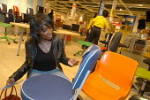 Ikea home furnishing store , customers shopping for home improvements. A woman looks at the price of furniture - Paul Box - 2000s,2004,BAME,BAMEs,black,BME,bmes,bought,BUY,buyer,buyers,buying,chair,chairs,commodities,commodity,consumer,consumers,Customer,customers,diversity,EBF Economy,ethnic,ethnicity,FEMALE,furnishing,fu