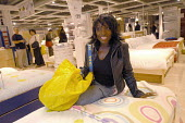 Ikea home furnishing store, customers shopping for home improvements. A woman sits on bed - Paul Box - 2000s,2004,BAME,BAMEs,black,BME,bmes,bought,BUY,buyer,buyers,buying,commodities,commodity,consumer,consumers,Customer,customers,diversity,EBF Economy,ethnic,ethnicity,FEMALE,furnishing,goods,home,ikea