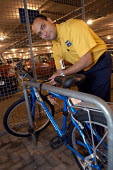 Ikea home furnishing store , a worker uses the companies cycles to get to work. pictured locking up his bike - Paul Box - 2000s,2004,assistants,companies,EBF Economy,employee,employees,Employment,ENVIRONMENT,environmental,environmental transport,europeregi,home,ikea,ikea employee,job,jobs,LAB LBR work,LBR,people,policy,r