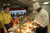Ikea home furnishing store , a black chef prepares food for the ikea staff restaurant - Paul Box - 2000s,2004,assistants,BAME,BAMEs,Black,BME,BME black,bmes,catering,chef chefs,chefs hat,customer service,diversity,EBF Economy,employee,employees,Employment,ethnic,ethnicity,europeregi,food,food hygen
