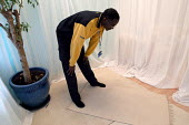 Ikea home furnishing store , a Muslim employee prays in the prayer room - Paul Box - ,2000s,2004,assistant,assistants,at,BAME,BAMEs,black,BME,bmes,diversity,EARNINGS,employee,EMPLOYEES,ethnic,ethnicity,home,ikea,Income,inequality,islam,islamic,job,jobs,LAB LBR work,living wage,Low Pay