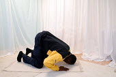 Ikea home furnishing store , a Muslim employee prays in the prayer room - Paul Box - 2000s,2004,assistant,assistants,at,BAME,BAMEs,black,BME,bmes,diversity,EARNINGS,employee,EMPLOYEES,EQUALITY,ethnic,ethnicity,home,ikea,Income,INCOMES,inequality,islam,islamic,job,jobs,LAB LBR work,liv