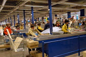 Ikea home furnishing store, a employee works at the check out - Paul Box - 2000s,2004,assistant,assistants,bought,buy,buyer,buyers,buying,checkout,commodities,commodity,consumer,consumers,Customer,Customers,EARNINGS,EBF,EBF Economy,Economic,Economy,FEMALE,flat,flatpack,furni