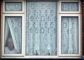 Resident looks out from behind the net curtains of her home, Lockleaze, Bristol where ASBO 's anti social behaviour orders have improved the area. - Paul Box - 30-06-2004