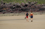 A couple walking down the beach on a hot day, Freshwater west, Pembrokeshire. - Paul Box - 20-08-2003