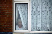 Resident looks out from behind the net curtains of her home, Lockleaze, Bristol where ASBO 's anti social behaviour orders have been issued in the area. - Paul Box - 2000s,2004,age,ageing population,anti social behavior,anti social behaviour,anti socialanti social behavior,antisocial,antisocial behaviour,antisocial behaviour order,antisocialvandalise,antisocialvan