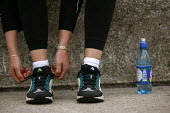 A runner prepares for fun run. Bristol - Paul Box - 2000s,2004,and,bottle,bottled,bottles,cardio,cardio vascular,cardiovascular,cities,city,exercise,exercises,exercising,FEMALE,fitness,health,healthy,heart,hydration,jog,jogger,joggers,jogging,laces,lfL
