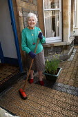 A 90 year old widowed woman sweeps her porch outside her home in Bristol. - Paul Box - 02-08-2004