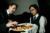 A chinese waitress serves food at a corporate event, Bristol. - Paul Box - 02-08-2004