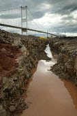 A sewage outlet pipe is cut through rock on the Severn estuary near the Severn bridge crossing. - Paul Box - 2000s,2004,bridge,Construction Industry,EBF economy,estuaries,estuary,jcb,job,jobs,LAB LBR Work,mud,muddy,people,pipe,pipeline,PIPES,sewage,sewer,SEWERAGE,sewers,site,SITES,trench,WASTE,water,worker,w