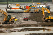 A sewage outlet pipe is cut through rock on the Severn estuary near the Severn bridge crossing. - Paul Box - 2000s,2004,boat,boats,bridge,Construction Industry,digger,diggers,EBF economy,estuaries,estuary,jcb,job,jobs,LAB LBR Work,people,pipe,pipeline,PIPES,river,sewage,sewer,SEWERAGE,sewers,site,SITES,tide,