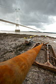 A sewage outlet pipe is cut through rock on the Severn estuary near the Severn bridge crossing. - Paul Box - 2000s,2004,bridge,Construction Industry,EBF economy,estuaries,estuary,job,jobs,LAB LBR Work,people,pipe,pipeline,pipes,sewage,sewer,SEWERAGE,sewers,site,SITES,trench,WASTE,worker,workers,working