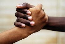 Black and mixed race handshake , Bristol. - Paul Box - 12-07-2004