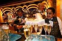 The Aurora cruise ship, a P&O cruise ship. Indonesian bar staff serve champagne. - Paul Box - 02-06-2004