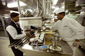 The Aurora cruise ship, a P&O cruise ship. An Indonesian chef at work in the kitchen.. - Paul Box - 2000s,2004,BAME,BAMEs,black,BME,bmes,catering,cook,COOKERY,cooking,cooks,crew,crewman,crewmen,crewmenmaritime,cruise,diversity,EBF economy,ethnic,ethnicity,foreign,foreigner,foreigners,galley,Hospital