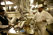 The Aurora cruise ship, a P&O cruise ship. Indonesian chef works in the kitchen. - Paul Box - 2000s,2004,BAME,BAMEs,black,BME,bmes,catering,cook,COOKERY,cooking,cooks,crew,crewman,crewmen,crewmenmaritime,cruise,diversity,EBF economy,ergonomic,ergonomics,ethnic,ethnicity,foreign,foreigner,forei