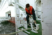 The Aurora cruise ship, a P&O cruise ship. Indonesian workers untie the tender. - Paul Box - 02-06-2004