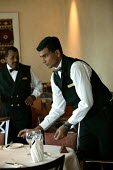 The Aurora cruise ship, a P&O cruise ship. Indonesian waiter at work. - Paul Box - 2000s,2004,BAME,BAMEs,black,BME,bmes,catering,crew,crewman,crewmen,crewmenmaritime,cruise,diversity,EBF economy,ethnic,ethnicity,foreign,foreigner,foreigners,Hospitality,international,job,jobs,LAB LBR