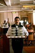 The Aurora cruise ship, a P&O cruise ship. Indonesian waiter at work. - Paul Box - 2000s,2004,a,BAME,BAMEs,black,BME,bmes,carries,carry,carrying,catering,crew,crewman,crewmen,crewmenmaritime,cruise,diversity,EBF economy,ethnic,ethnicity,foreign,foreigner,foreigners,Hospitality,inter