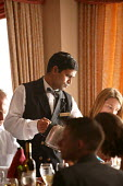 The Aurora cruise ship, a P&O cruise ship. Indonesian waiter takes a food order. - Paul Box - 2000s,2004,BAME,BAMEs,black,BME,bmes,catering,crew,crewman,crewmen,crewmenmaritime,cruise,diversity,EBF economy,ethnic,ethnicity,food,FOODS,foreign,foreigner,foreigners,good,Hospitality,international,