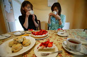 Friends share tea and cakes. - Paul Box - 2000s,2004,a,BAME,BAMEs,Black,BME,bmes,cake,cakes,chinese,cup,cups,Diaspora,diversity,drink,drinking,drinks,eating,ethnic,ethnicity,food,FOODS,foreign,foreigner,foreigners,Friends,gastronomy,good,immi