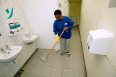 A toilet attendant cleaning, London - Paul Box - ,2000s,2004,attendant,ATTENDANTS,BAME,BAMEs,black,BME,bmes,cities,city,clean,cleaner,cleaners,cleaning,cleansing,Council Services,Council Services,diversity,EARNINGS,EBF economy,EQUALITY,ethnic,ethnic