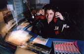 A teenager sitting in a studio at a local radio station for work experience. - Paul Box - 2000s,2004,adolescence,adolescent,adolescents,asian,BAME,BAMEs,black,BME,bmes,communicating,communication,desk,disk,disks,diversity,DJ,ethnic,ethnicity,headphones,job,jobs,jocky,LAB LBR Work,local,med